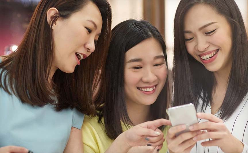 3 Chinese consumers looking at a smartphone