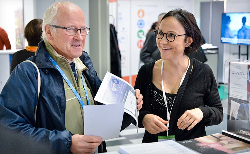 A member of the shareholder relations team talking to an attendee at the Actionaria Shareholder Fair